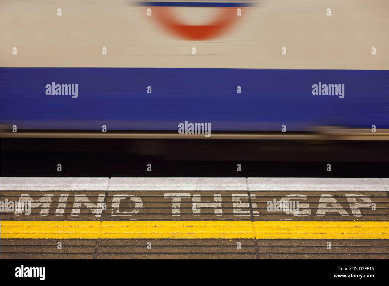 Bank underground station 'Mind the Gap' sign painted on the station platform with fast moving tube train - Stock Image