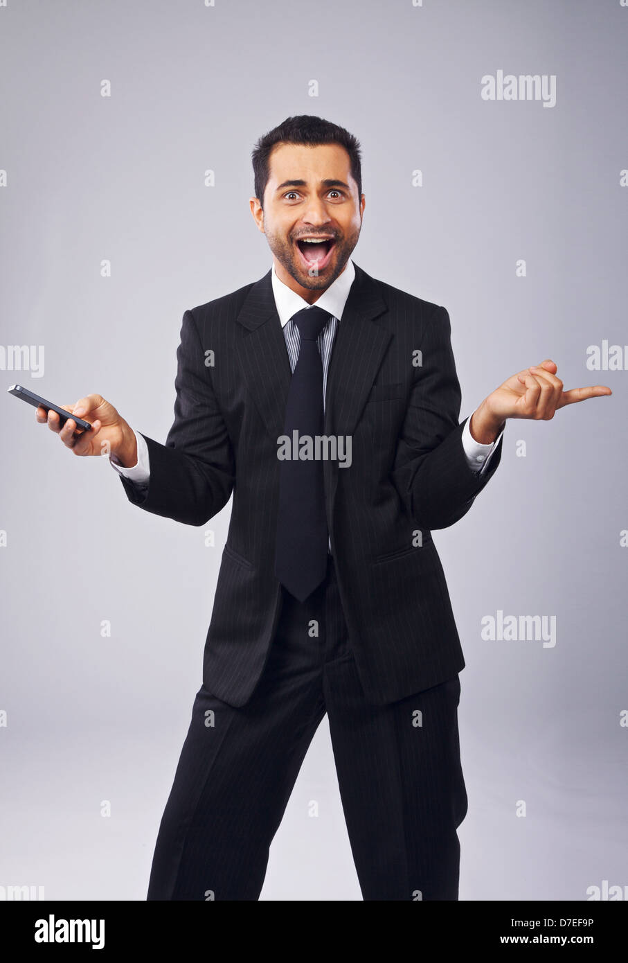 Cheerful young professional holding a phone while gesturing - Stock Image