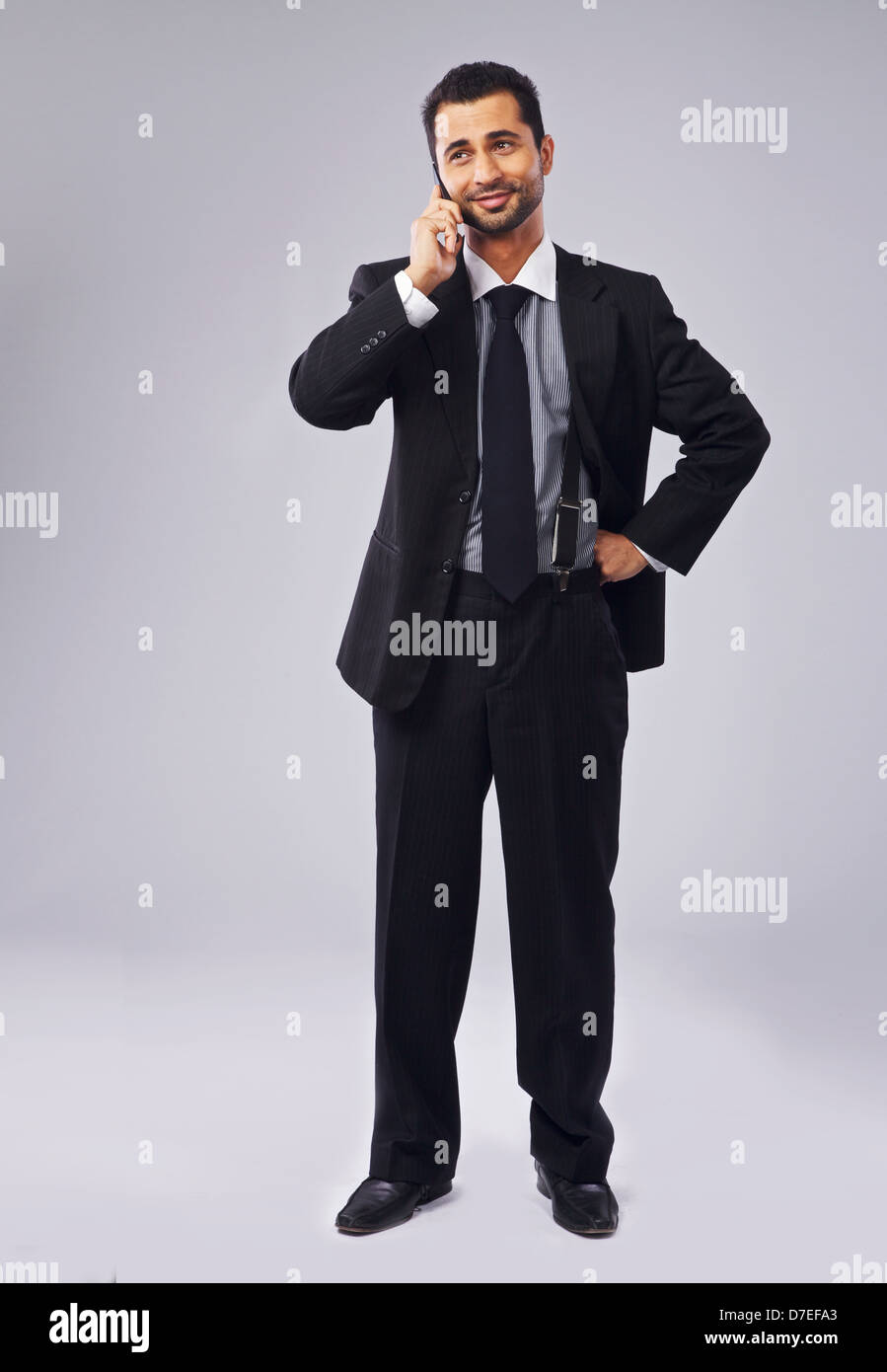 Full length of a handsome young executive talking on the phone - Stock Image