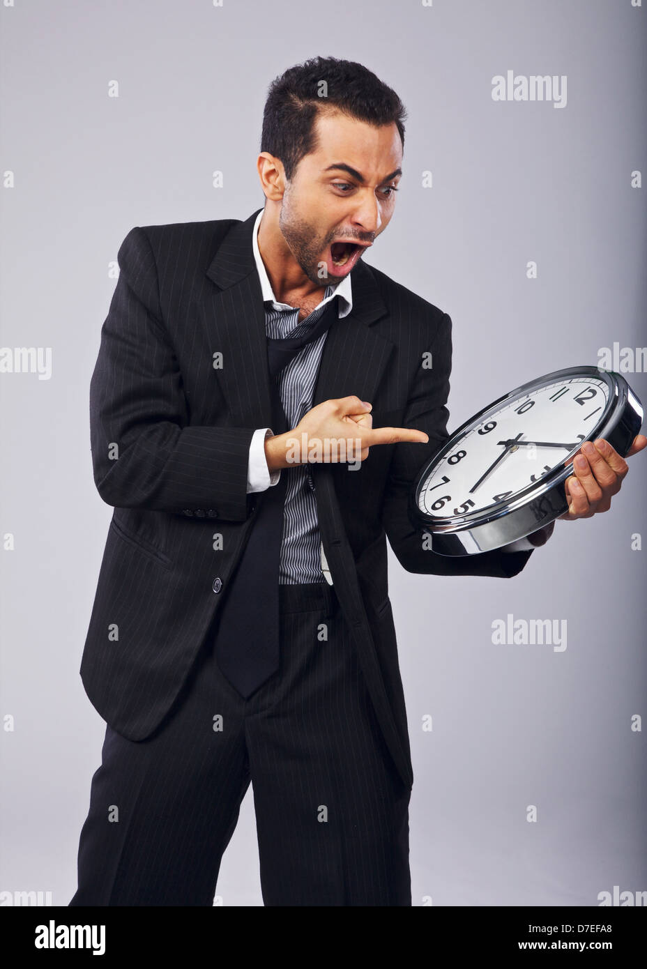 Angry businessman shouting and pointing to a clock - Stock Image