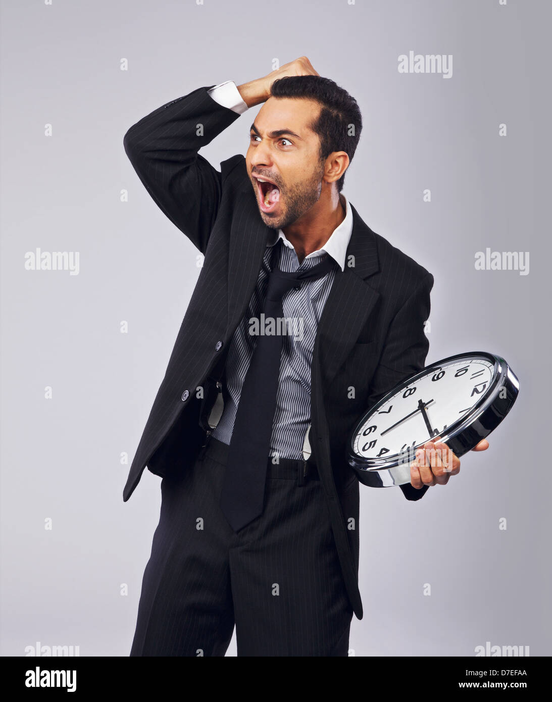 Businessman in panic for not meeting the deadline - Stock Image