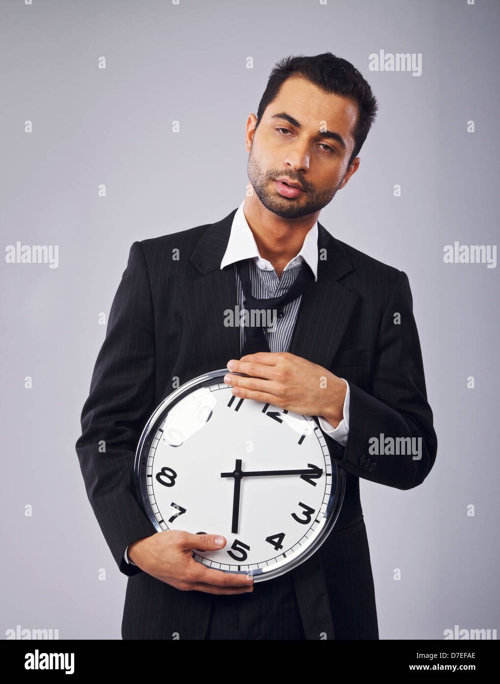 Sleepy office worker holding a clock - Stock Image
