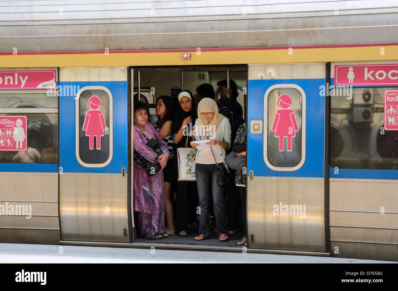 Women only carriage on a local city commuter train; woman only carriage; standing room only; train coach; doors - Stock Image