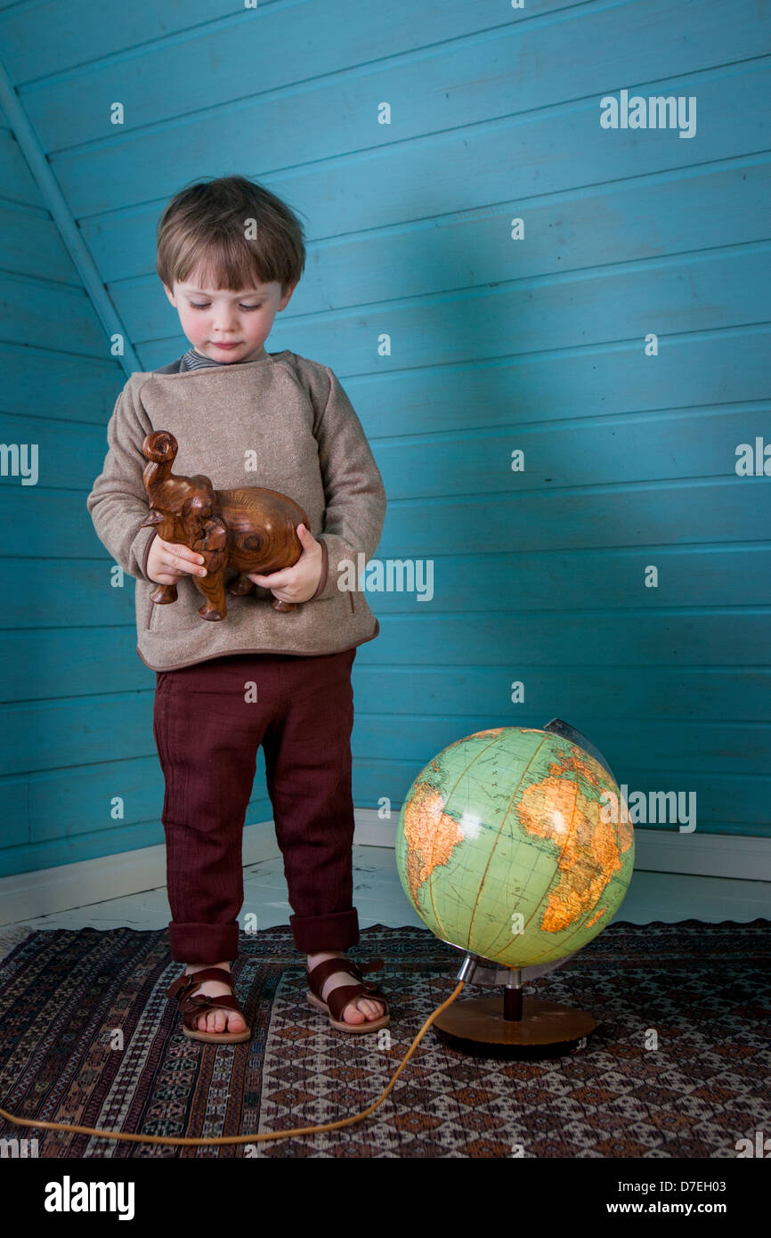 Little boy looking at a wooden carved elephant in his hands standing next to a illuminated globe showing Africa - Stock Image