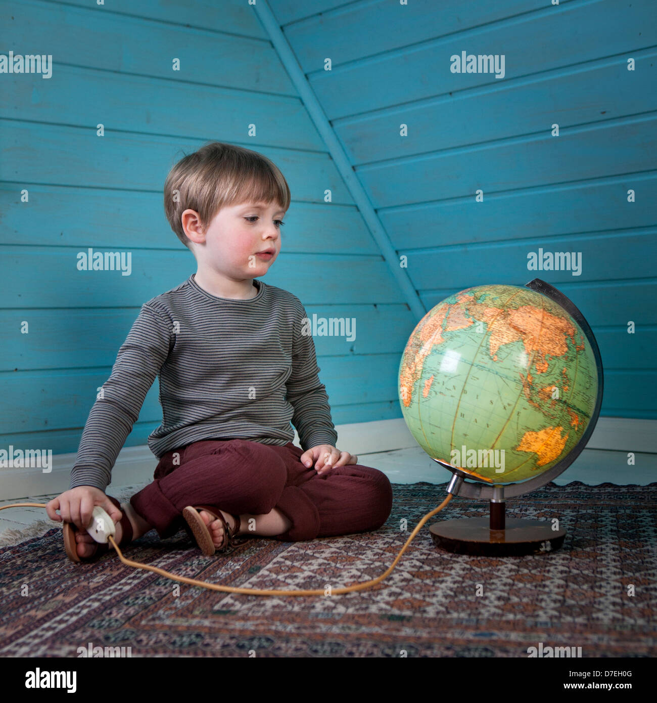 A young child looks at a lit up globe thinking about far away places sitting in a cosy attic room at home light - Stock Image