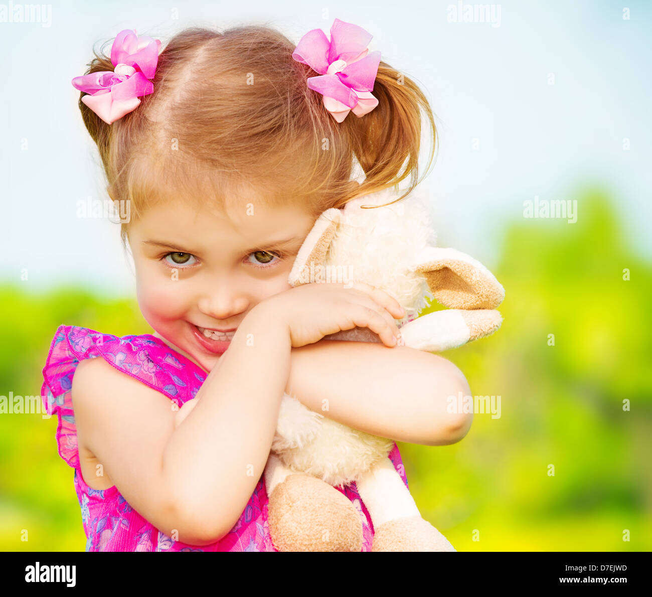 Happy smiling girl with lovely soft toy in the garden in daycare, having fun outdoors, spring season, happy childhood - Stock Image