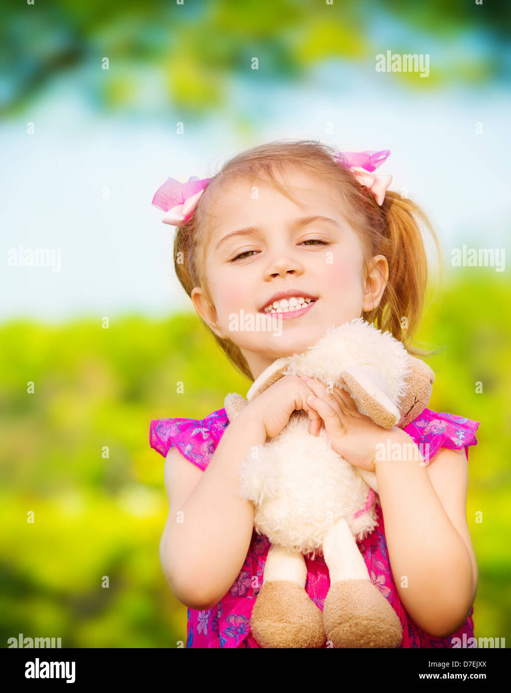 Sweet little girl hug soft toy outdoors in spring time, playing game on backyard, day care, happy childhood concept - Stock Image
