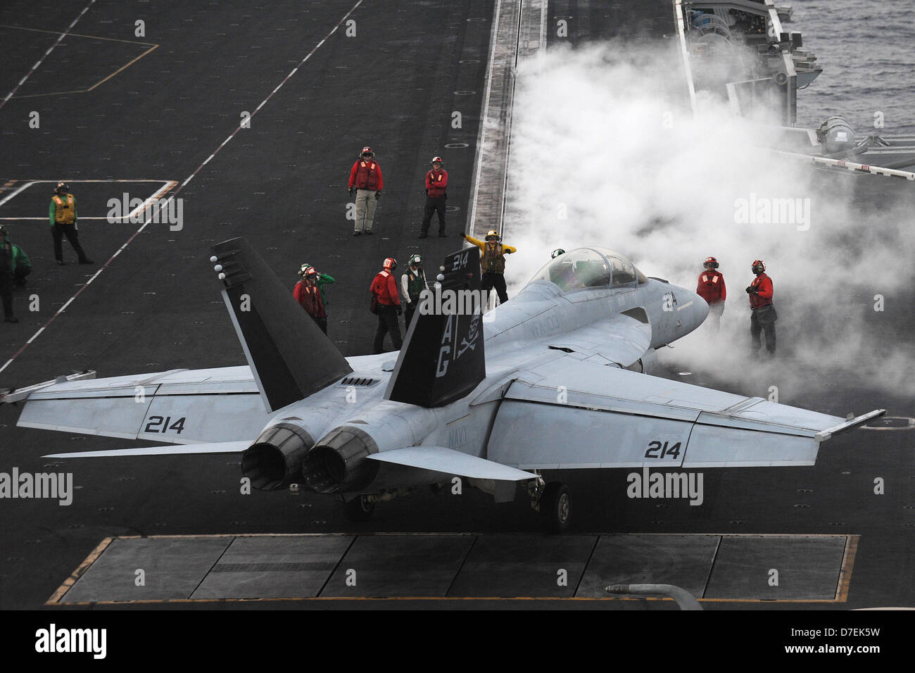 An F/A-18F is directed to a catapult at sea. - Stock Image