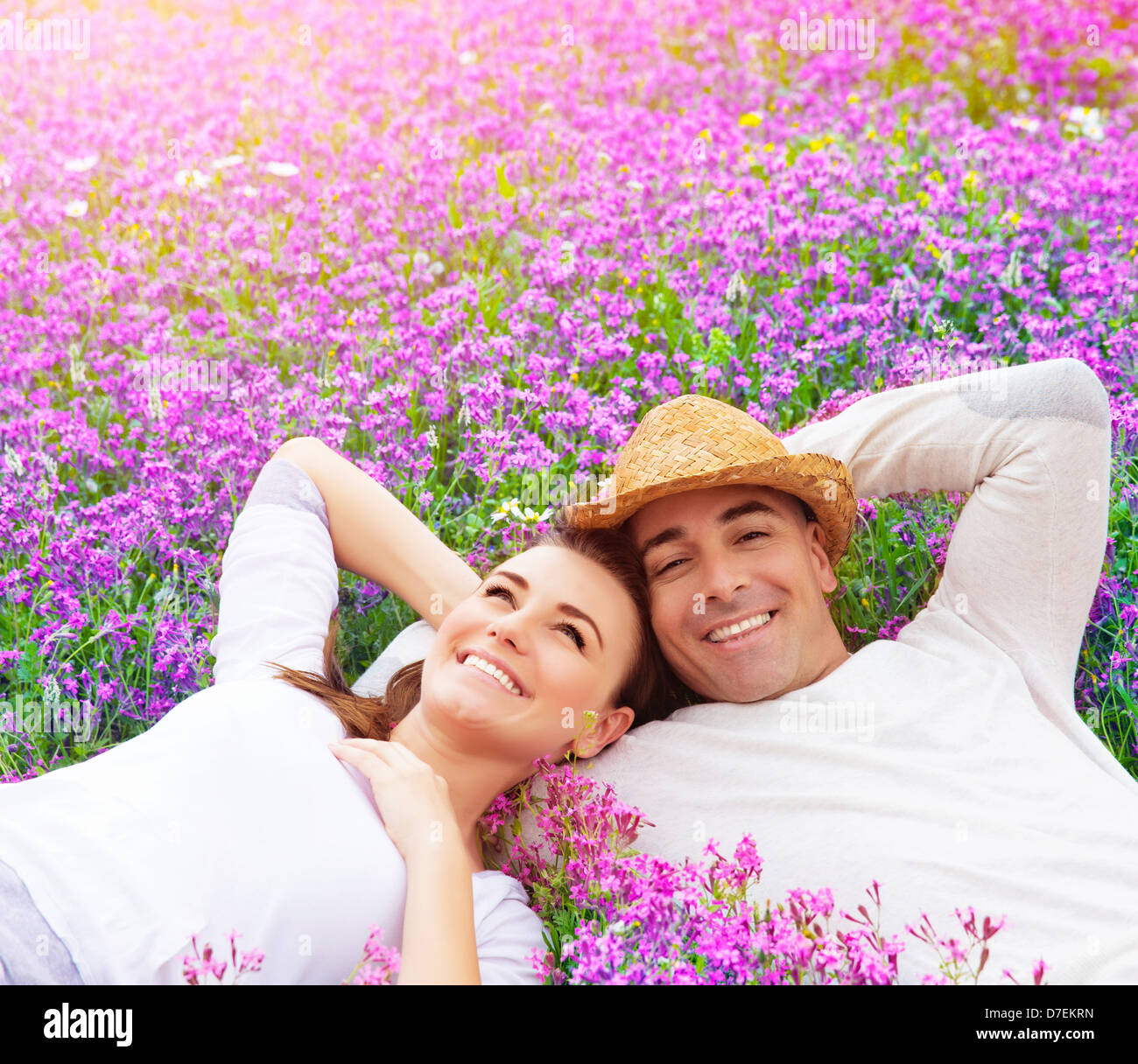 Beautiful happy couple lying down on purple lavender field, having fun on floral glade, summer nature, love concept - Stock Image