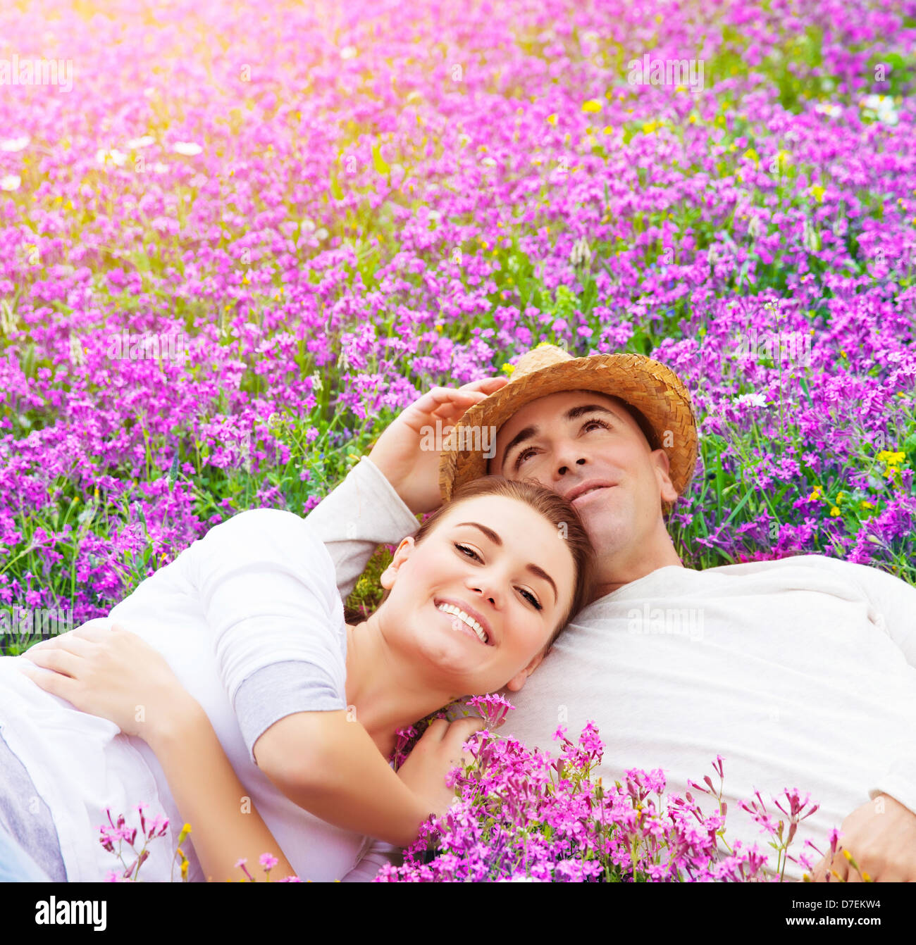 Young happy family laying down on fresh lavender meadow, hugging outdoors, summer season, romance and love concept - Stock Image