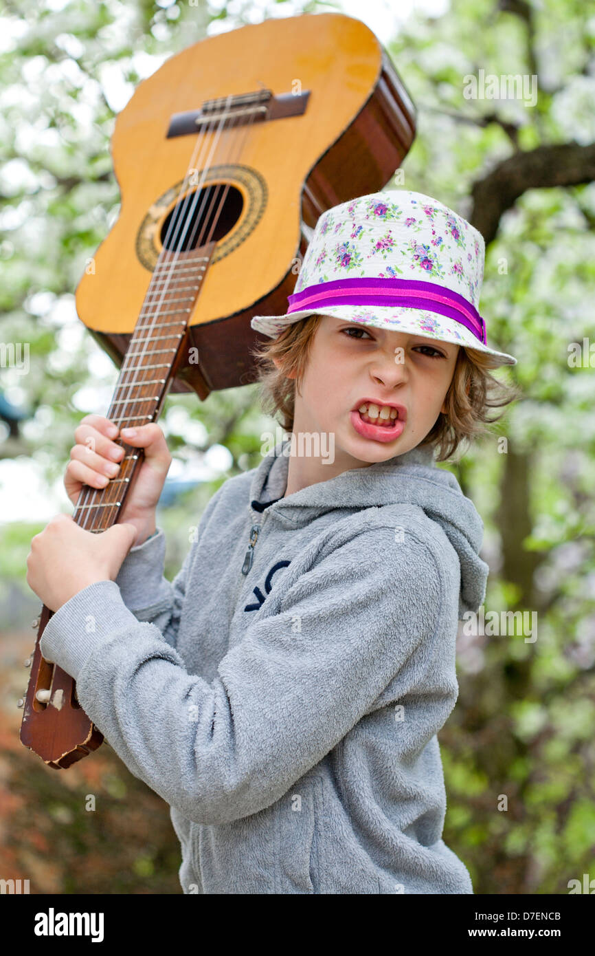 Portrait of a boy playing an acoustic guitar outdoor in the garden. Stock Photo