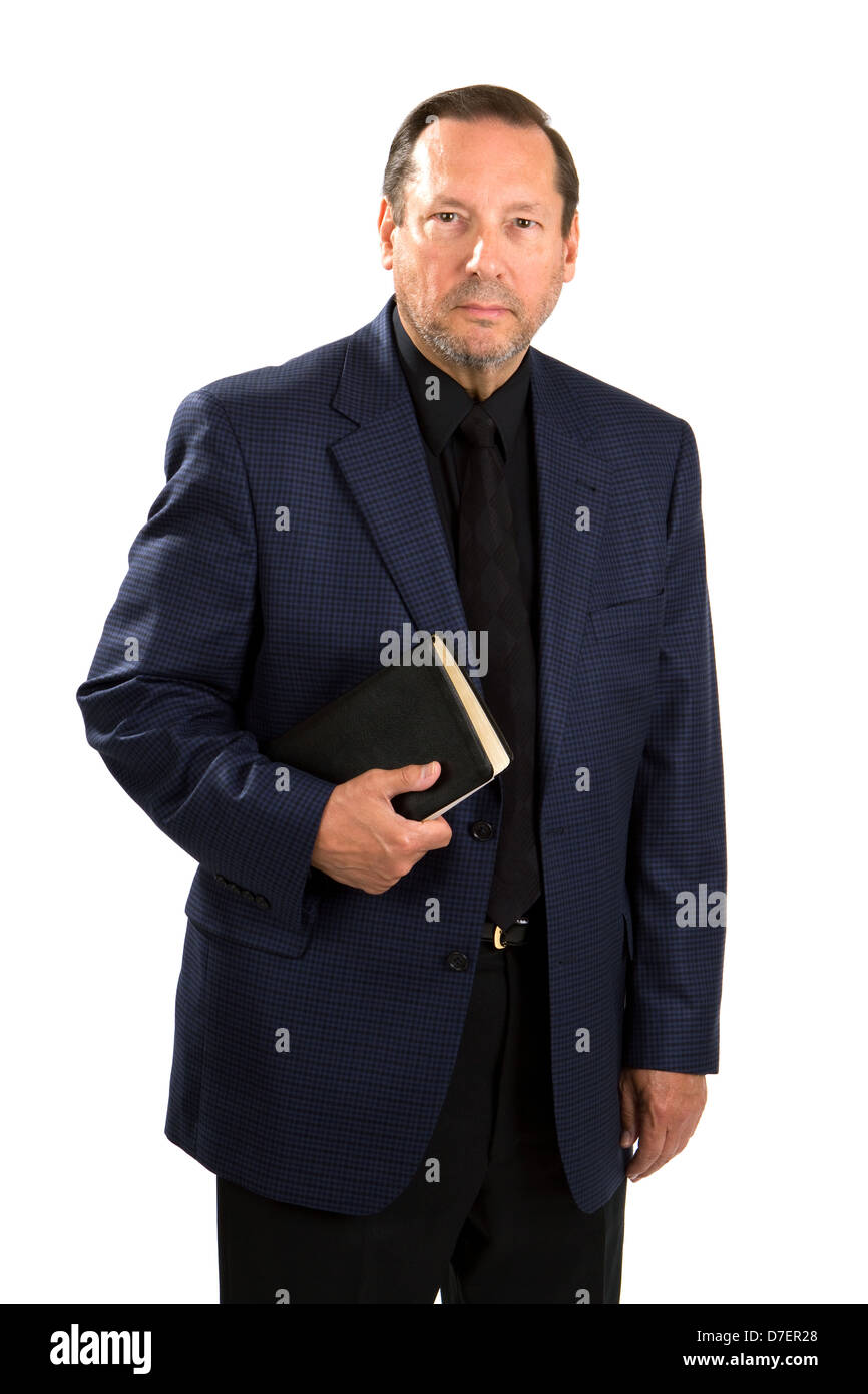 Senior adult pastorial staff in a blue sports coat holds his Holy Bible. - Stock Image