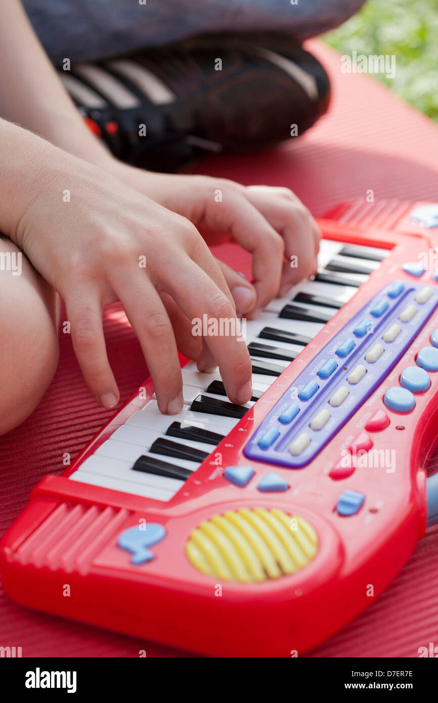 Portrait of a boy with keyboard playing outdoor in the garden. - Stock Image