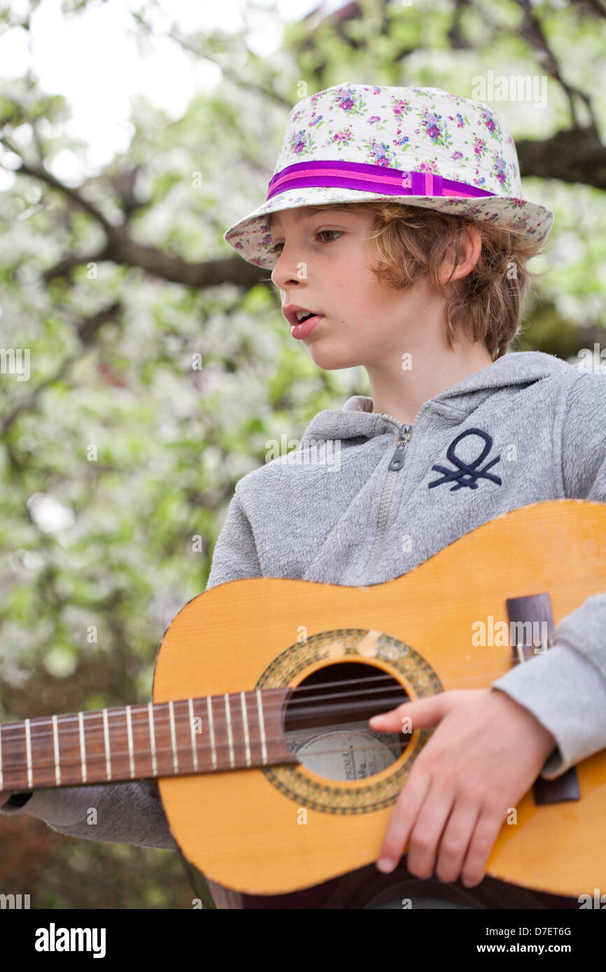 Portrait of a Boy playing an acoustic guitar outdoor in the garden. - Stock Image