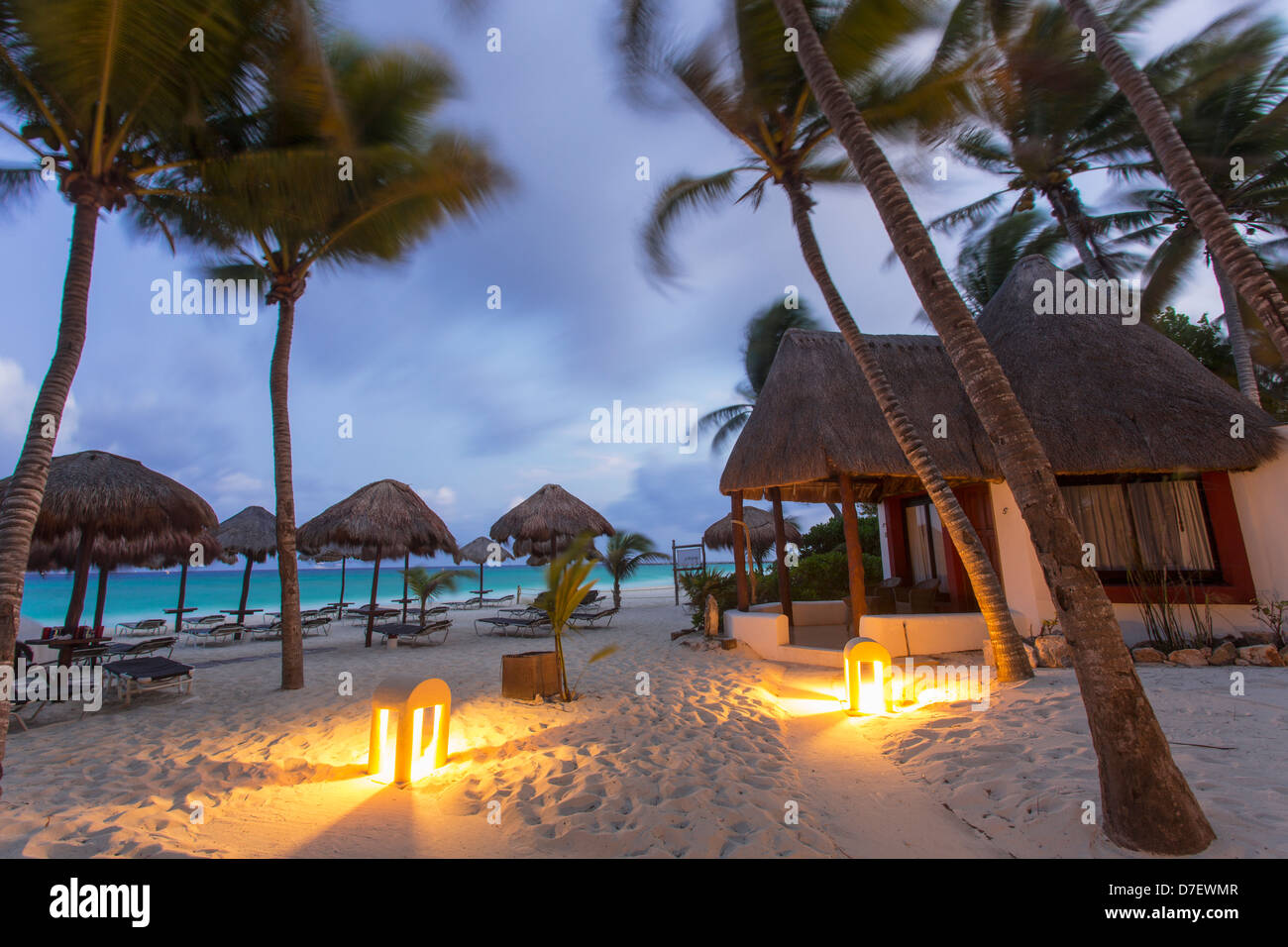 cabana style accommodation on the beach surrounded by palm trees at dawn - Stock Image