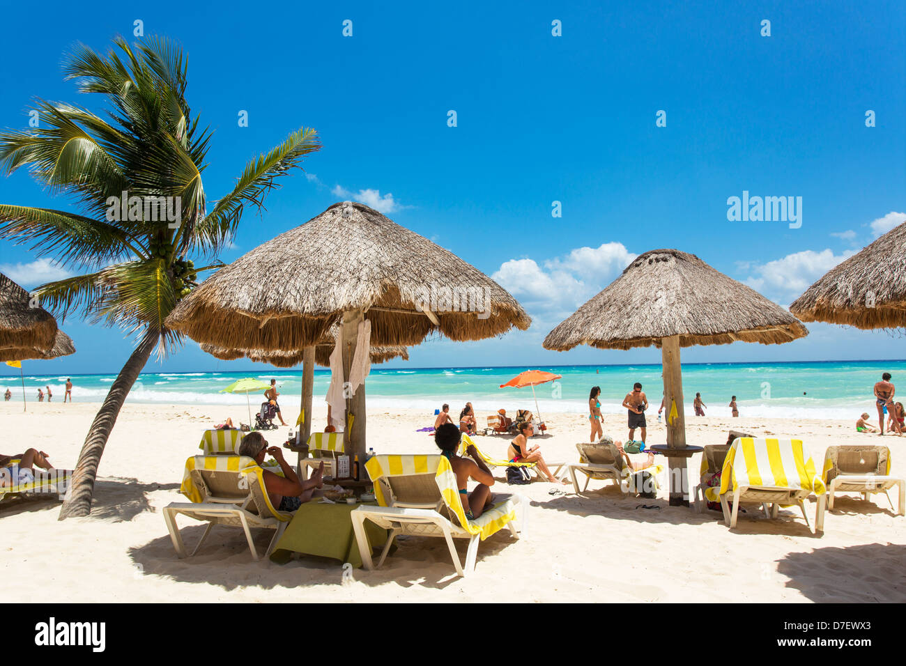 Mexico, Playa del Carmen people at a beach with palm trees and palapas - Stock Image