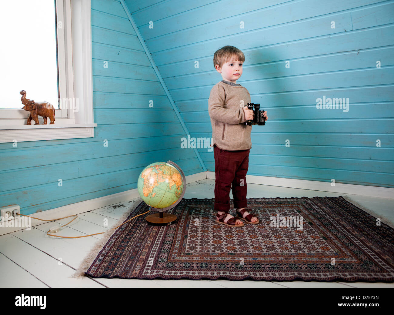Little boy holding binoculars in his hands standing next to a illuminated globe showing and wooden carved elephant - Stock Image