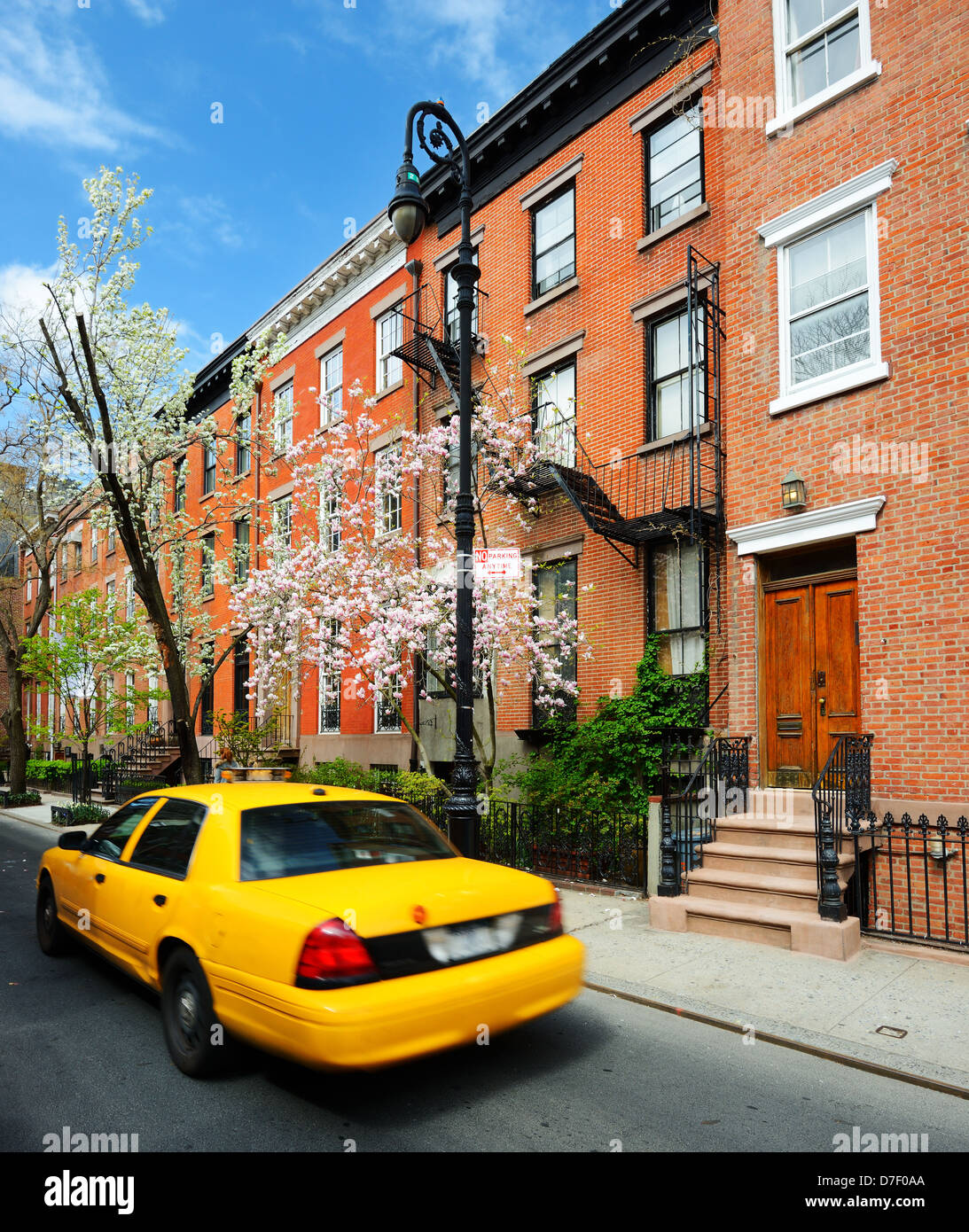 Yellowcab passes by Greenwich Village apartments in New York City. - Stock Image