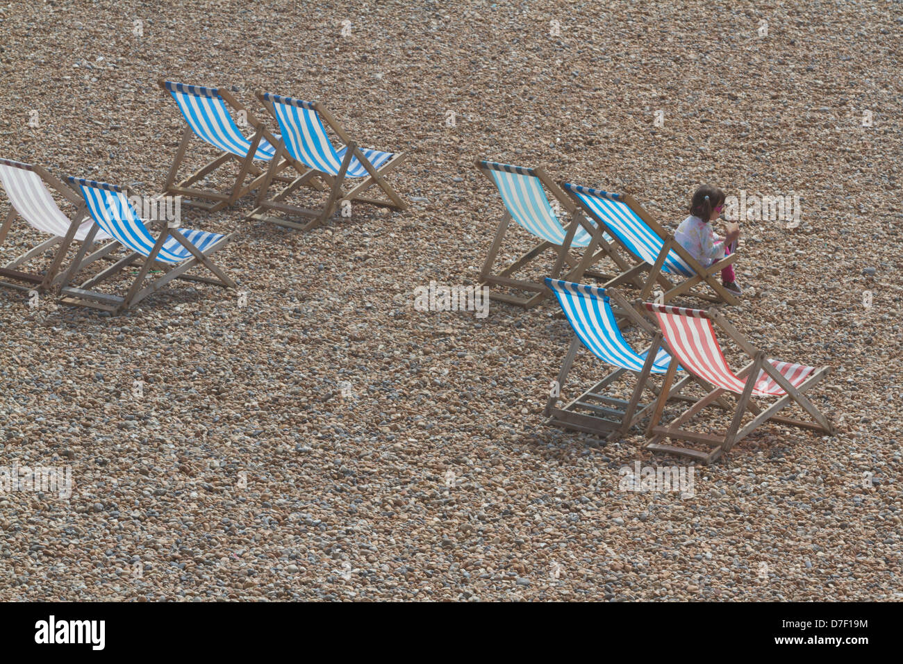 6th May 2013. Brighton UK.  A young beach goer sits on a deckchair on Brighton beach on a bank holiday  as temperatures - Stock Image