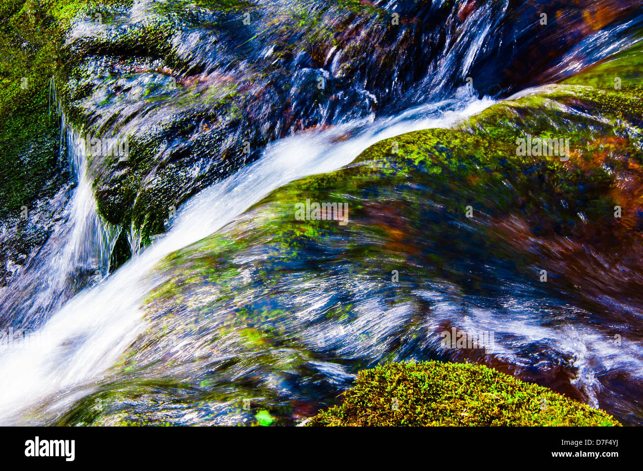 Crystal clear water flowing over green mossy rocks - Stock Image