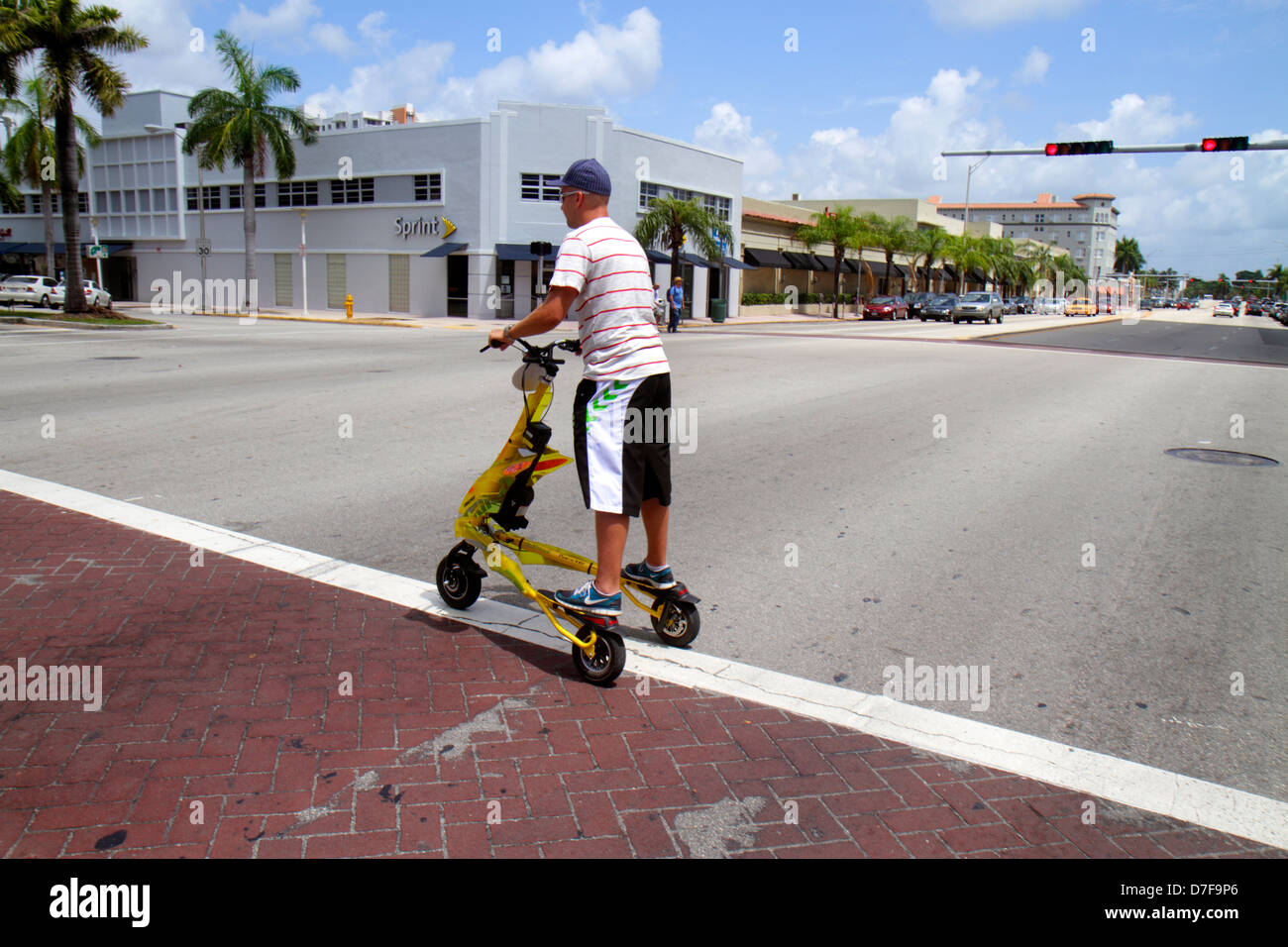 Miami Beach Florida Alton Road Tribred by Trikke electric vehicle rented rental Hispanic man riding traffic intersection - Stock Image