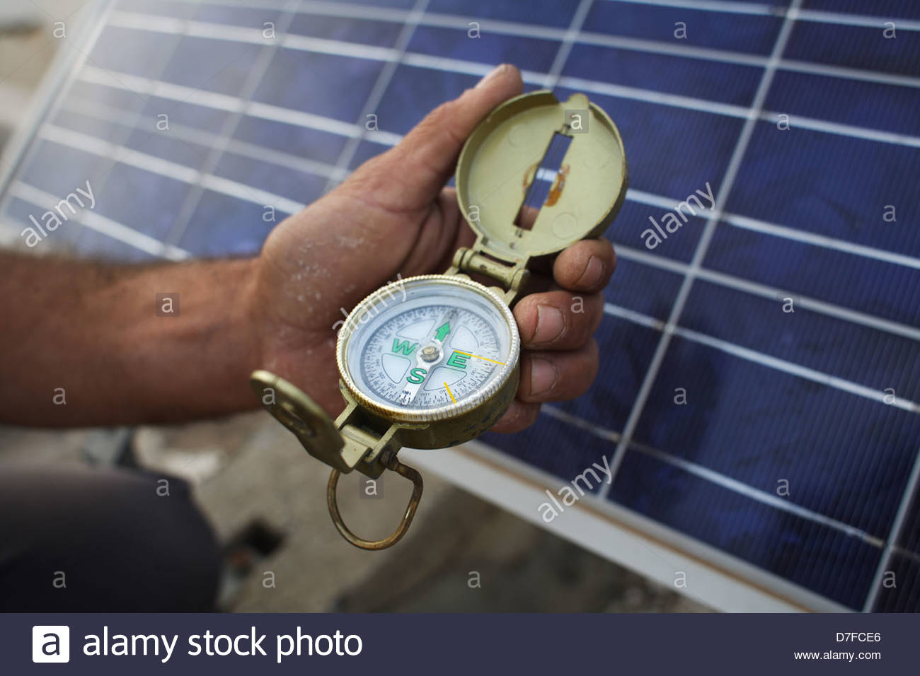 Human hand holds a compass near solar panel, Oulad, Morocco - Stock Image