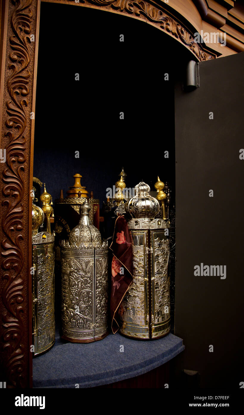 An Open Cabinet With Several Torah (old Testament) Scrolls Closed In Gold  And Silver Fancy Containers.