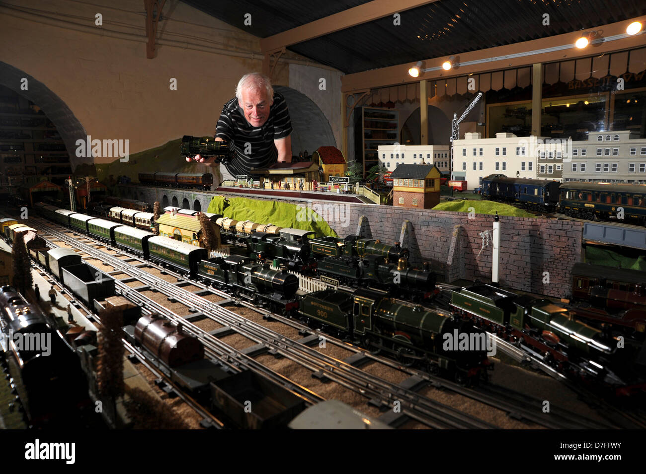 Brighton, Sussex, UK. 7th May 2013. Chris Littledale places a Hornby model train on the track at Brighton Toy Museum Stock Photo