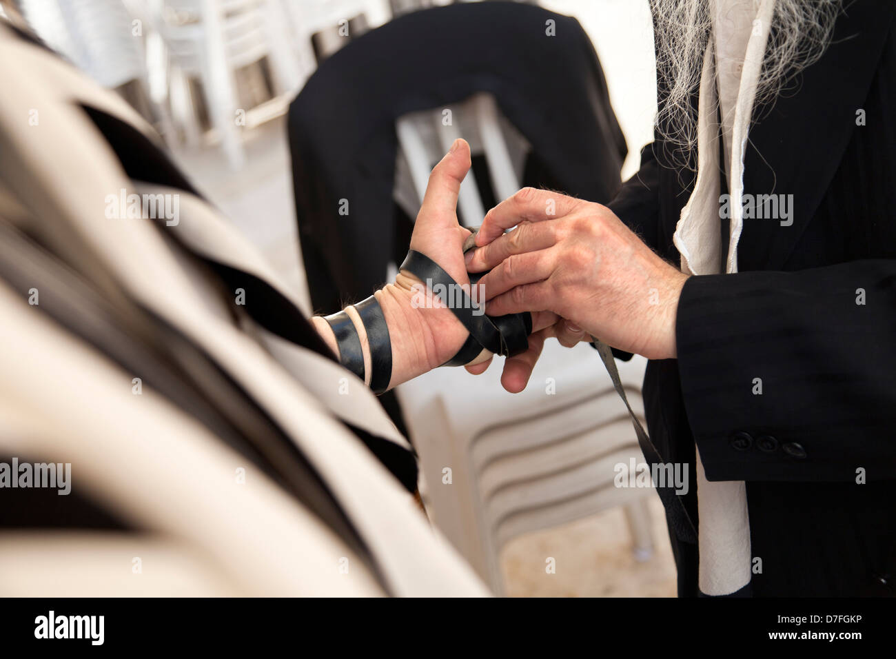 The hand an adult Caucasian man is being wrapped in leather strap part Jewish phylacteries (Teffilin Tefilin Tfilin) - Stock Image