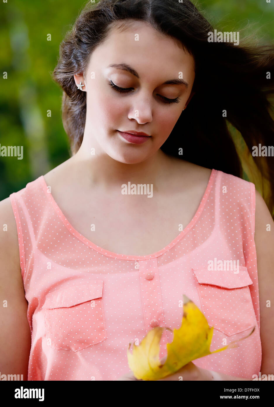 Young teenage girl looks deeply at the autumn leaf - Stock Image