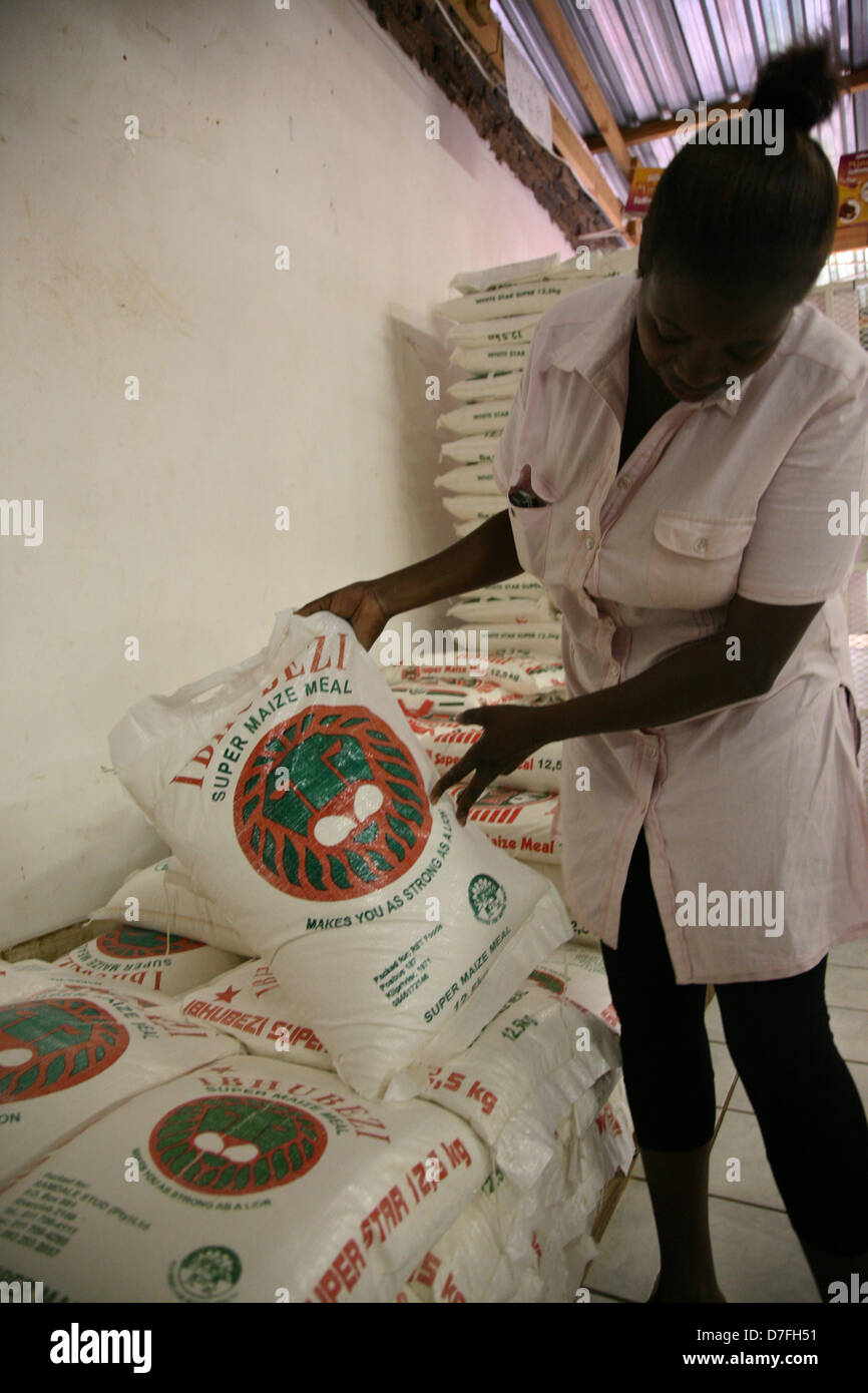 An African female consumer chooses a 12.5kg bag of maize meal - Stock Image