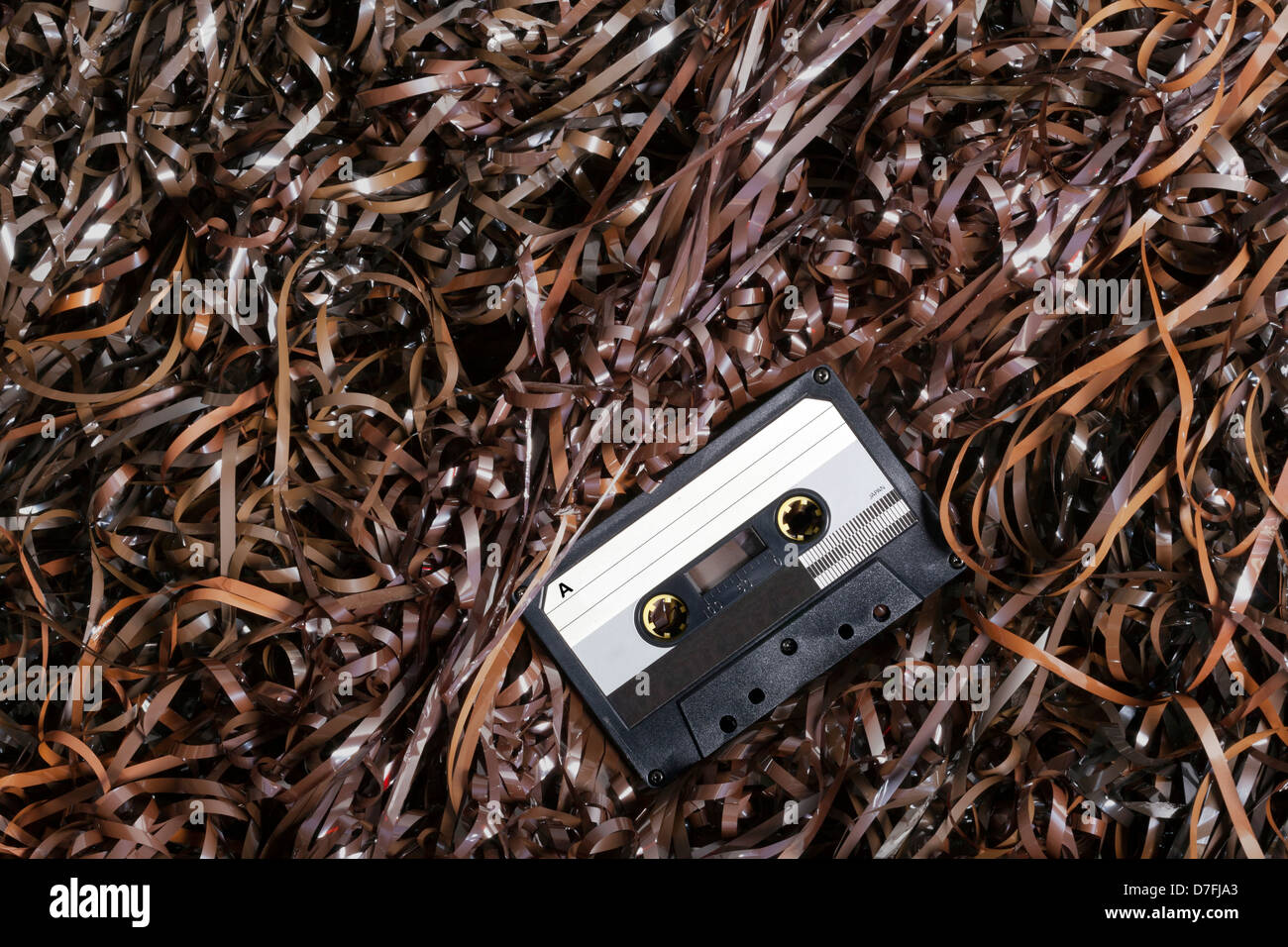 Black recordable plastic audio cassette resting on a large amount of magnetic audio tape. - Stock Image