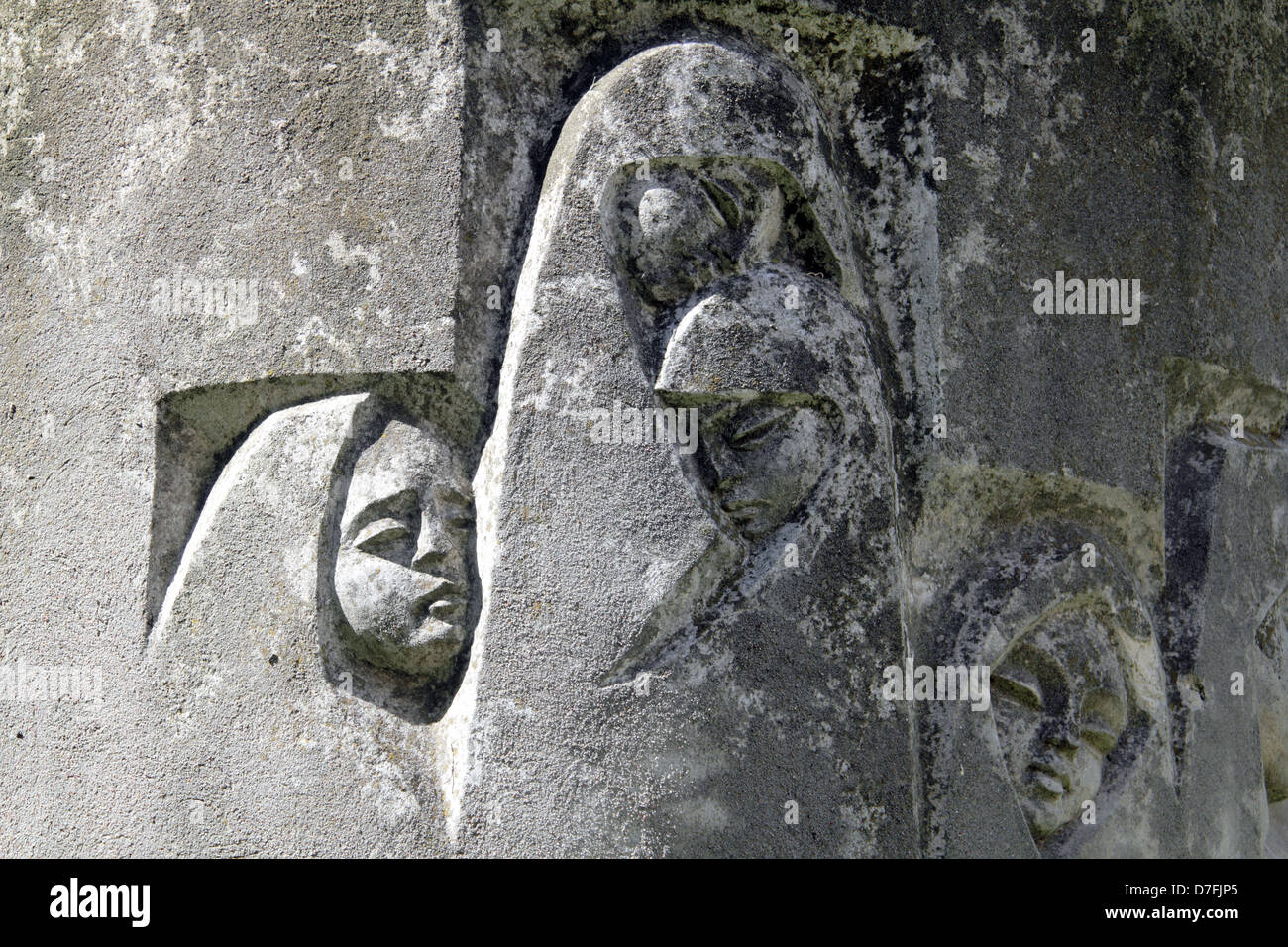 Orphans' faces engraved on a section of Janusz Korczak Sculpture In Front Of The Krochmalna Street Orphanage - Stock Image