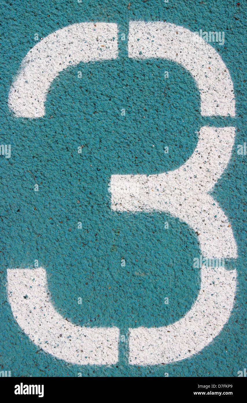digit 3 on a blue athletics track - Stock Image