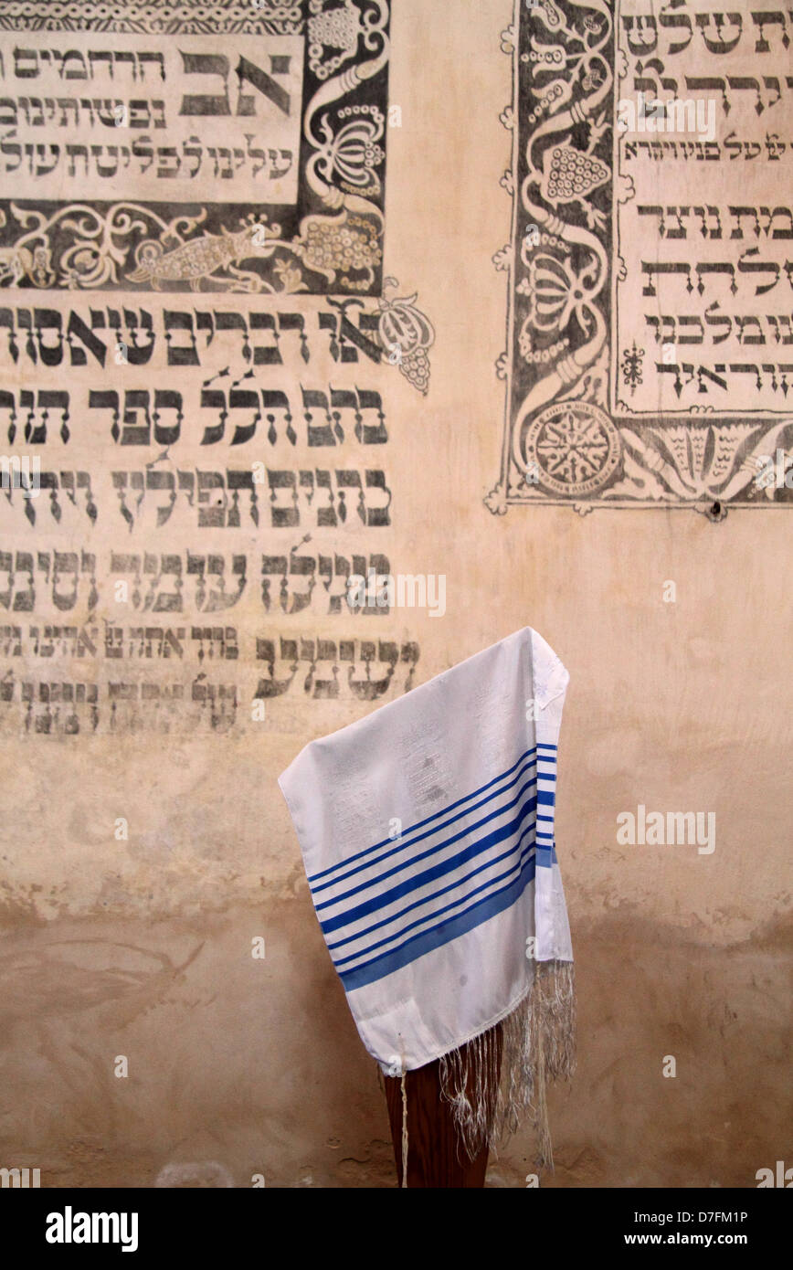 Prayer shawl (Tallit) and Jewish prayers written in Hebrew on the wall at Tykocin (Tiktin) synagogue, Poland - Stock Image