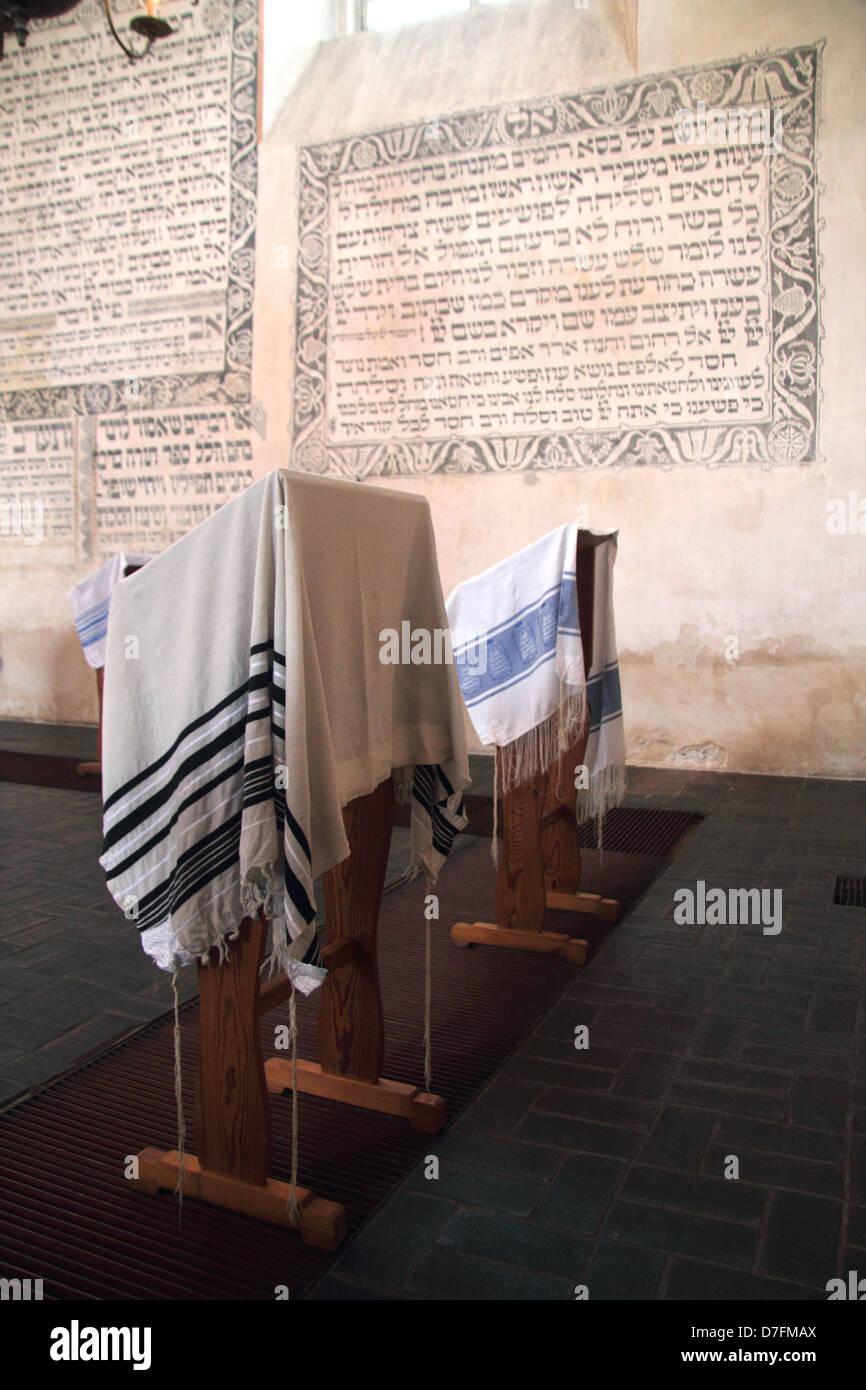 Prayer Shawls (Tallit) And Jewish Prayers Written In Hebrew On The Wall At Tykocin (Tiktin) Synagogue, Poland - Stock Image