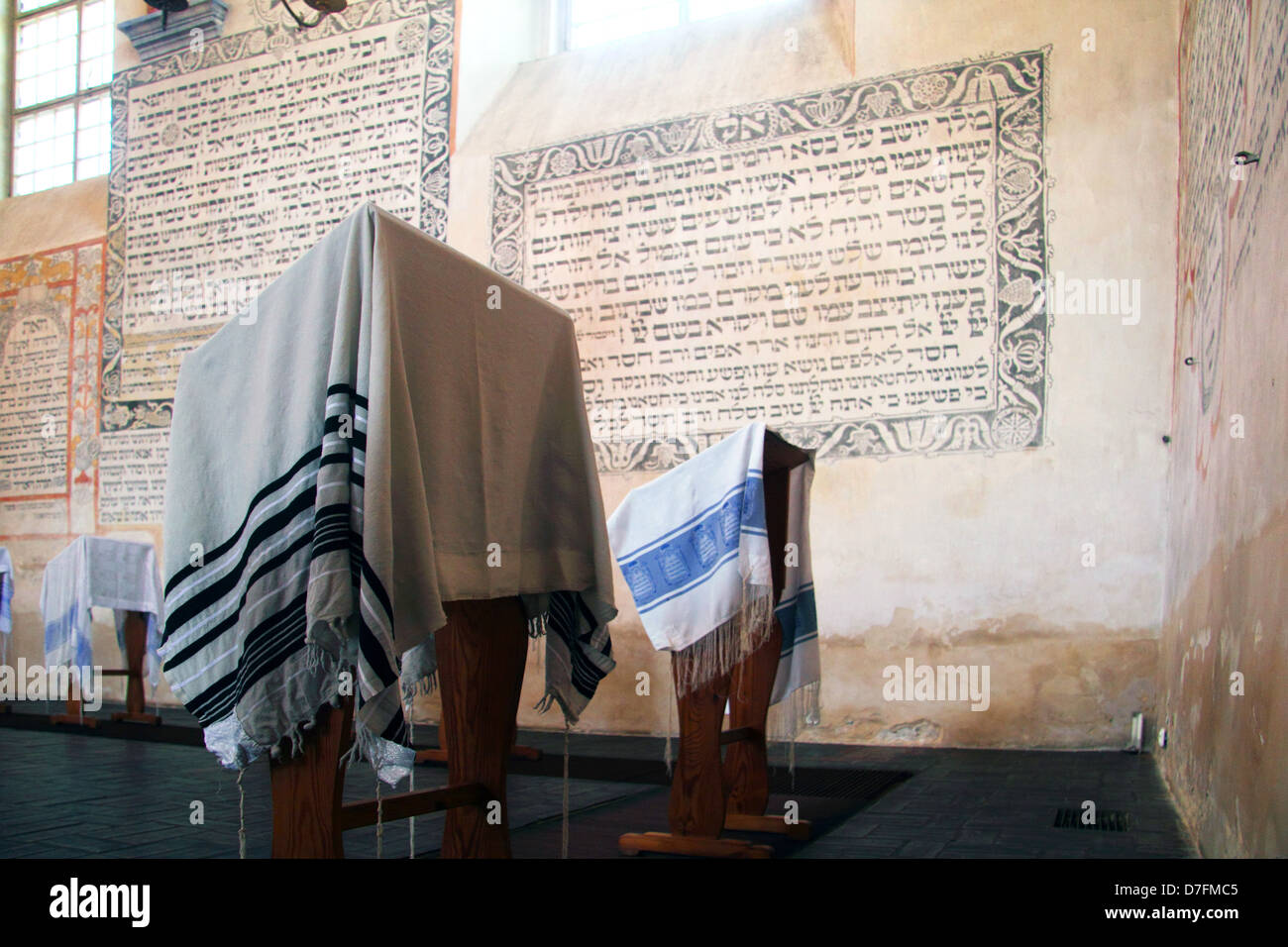 Prayer Shawls (Tallit) And Jewish Prayers Written In Hebrew On The Wall At Tykocin (Tiktin) Synagogue - Stock Image