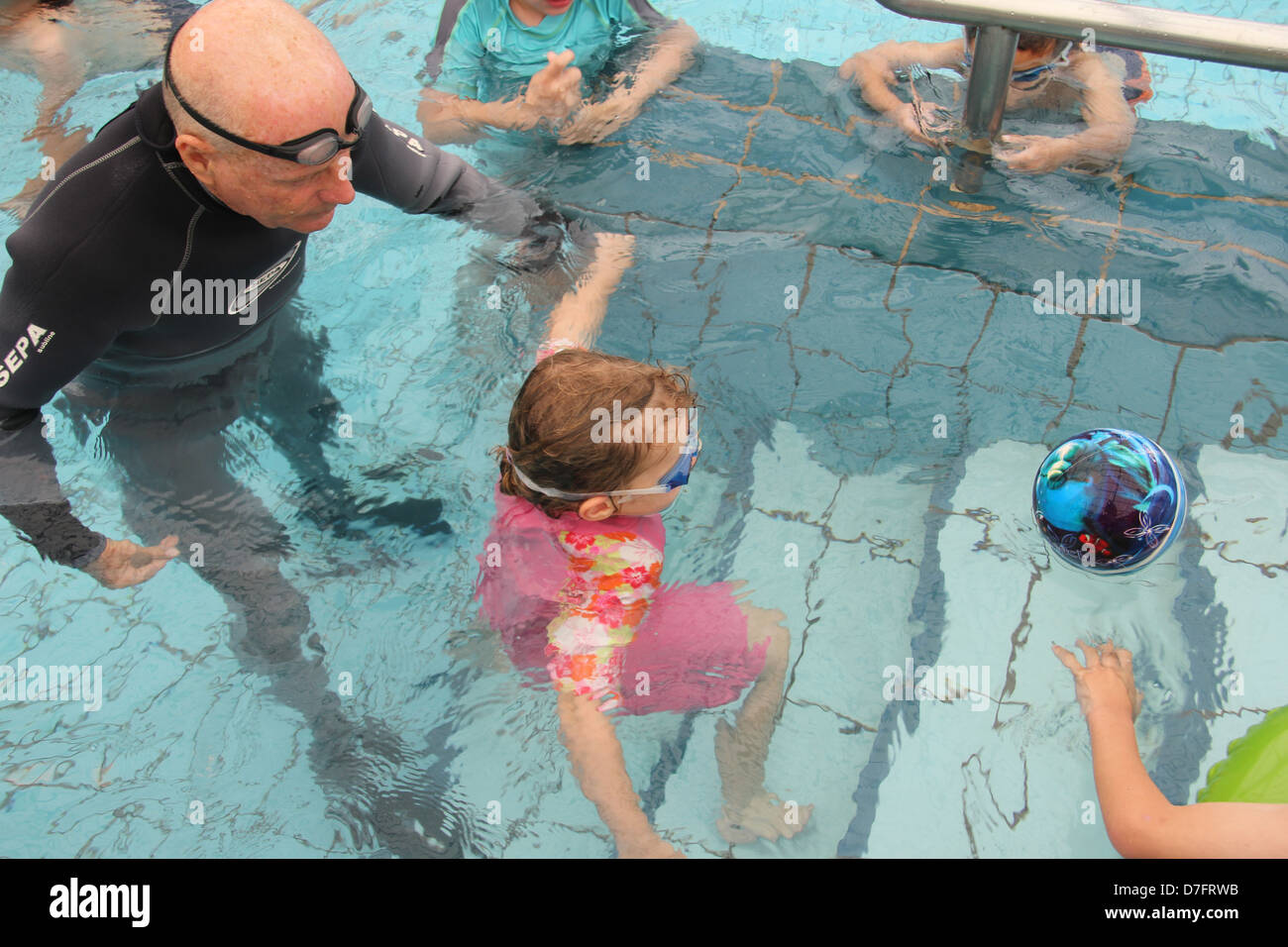 Child practising Hydrotherapy (hydropathy) in swimming pool, Misgav - Stock Image