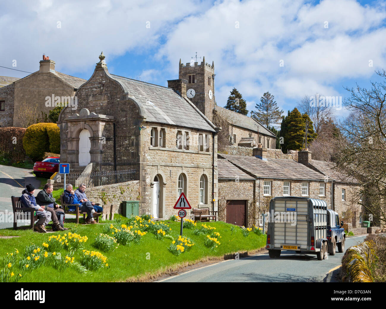 Horse box being driven through the village watched by four walkers sat on a bench Muker North Yorkshire Dales National - Stock Image