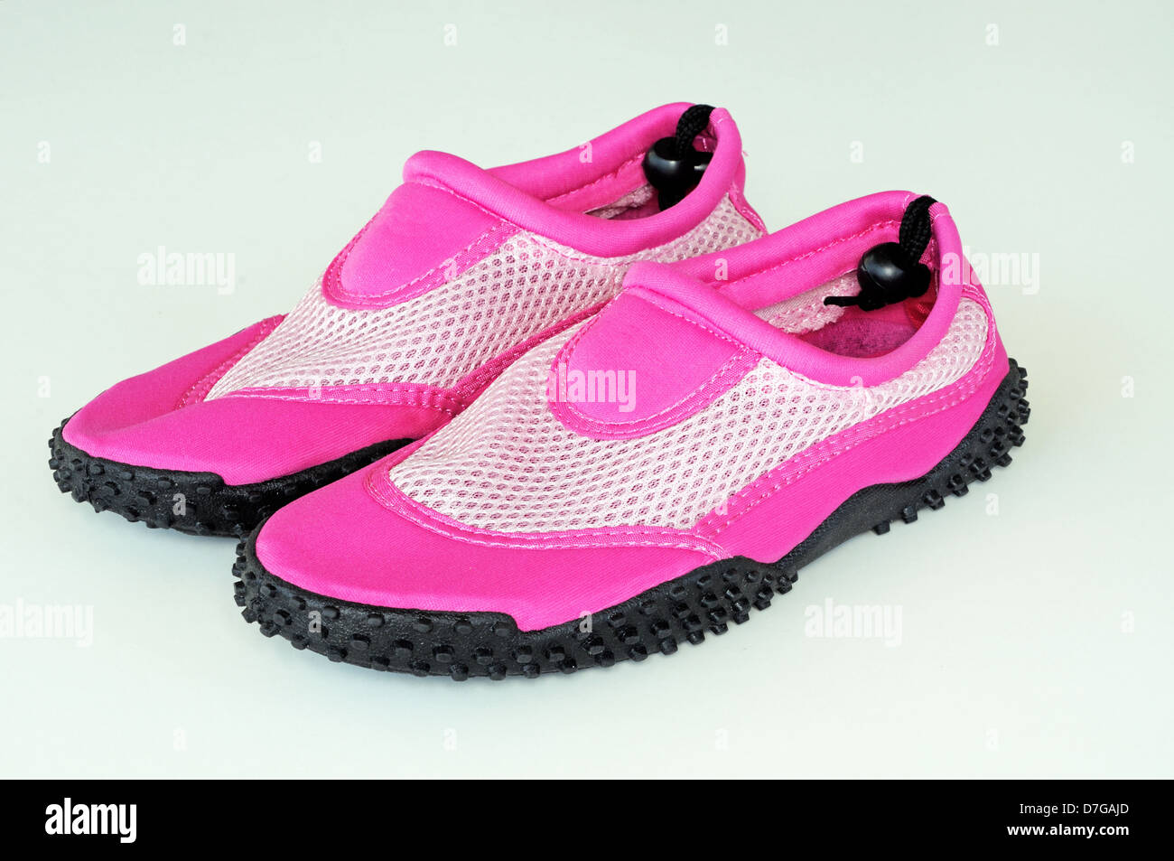 Ladies pink beach shoes against a plain background. - Stock Image