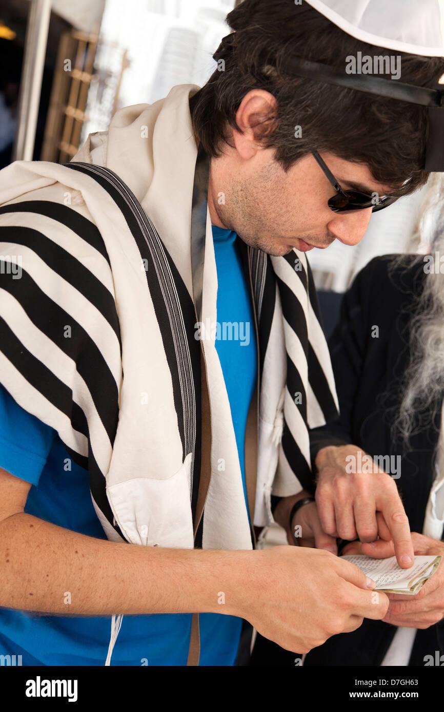 An adult Caucasian Jewish man wearing praying shawl Yarmulke Phylacteries while being helped by Rabbi praying. This - Stock Image