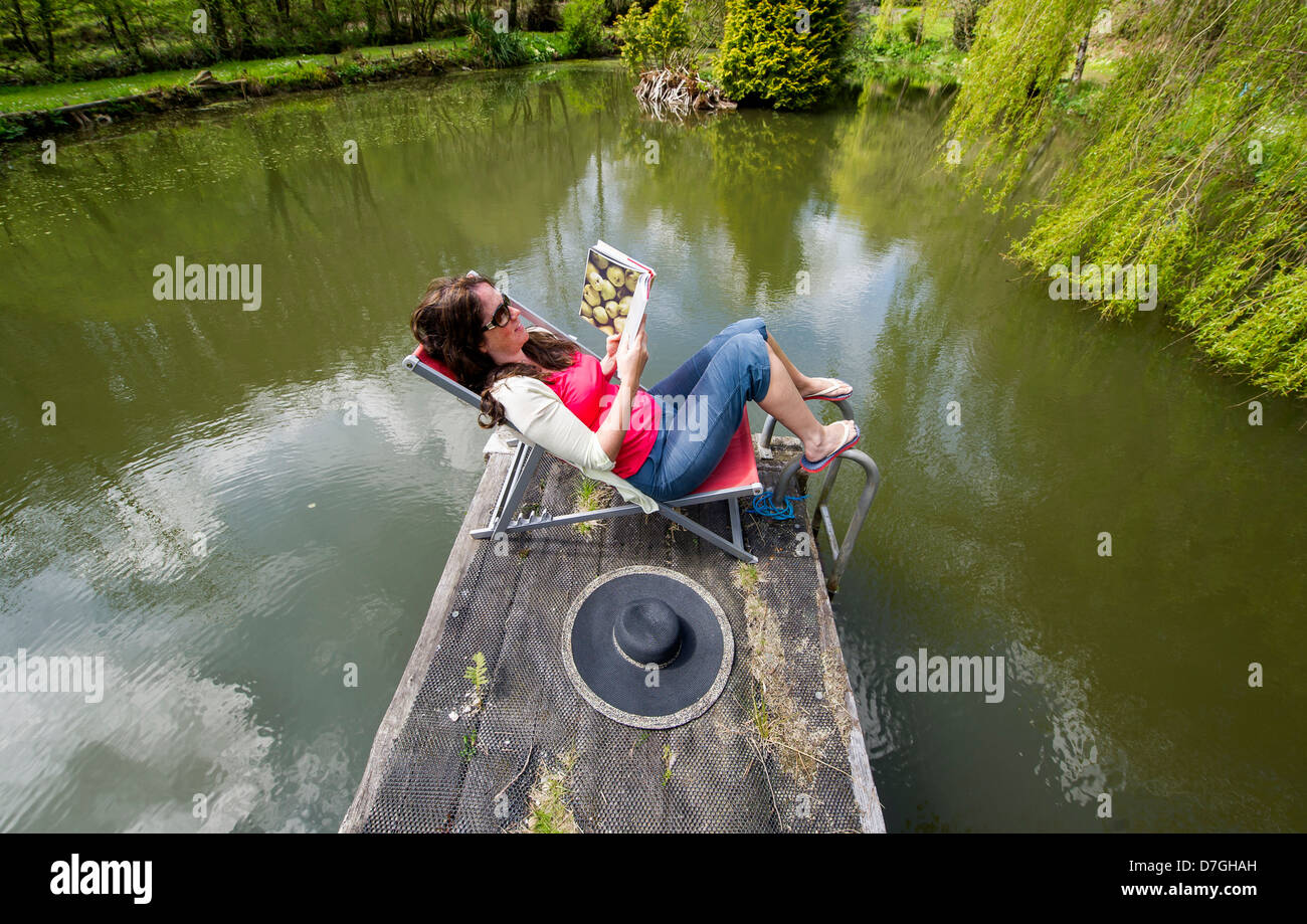 A woman keeps cool in the sunshine as temperatures rise across the UK on a May Bank Holiday, Devon UK - Stock Image