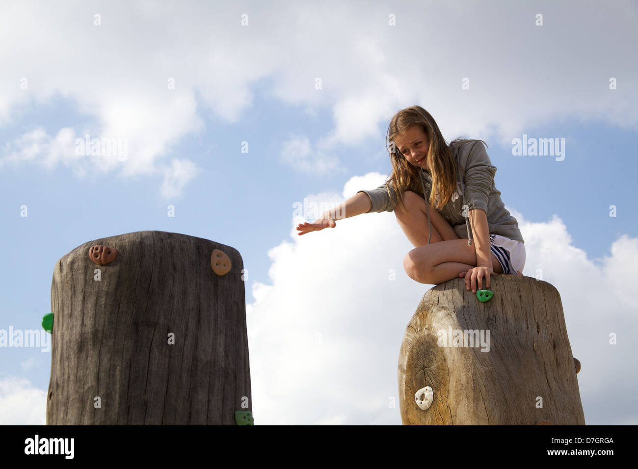 girl balancing on tree trunk attempting reach across a divide - Stock Image