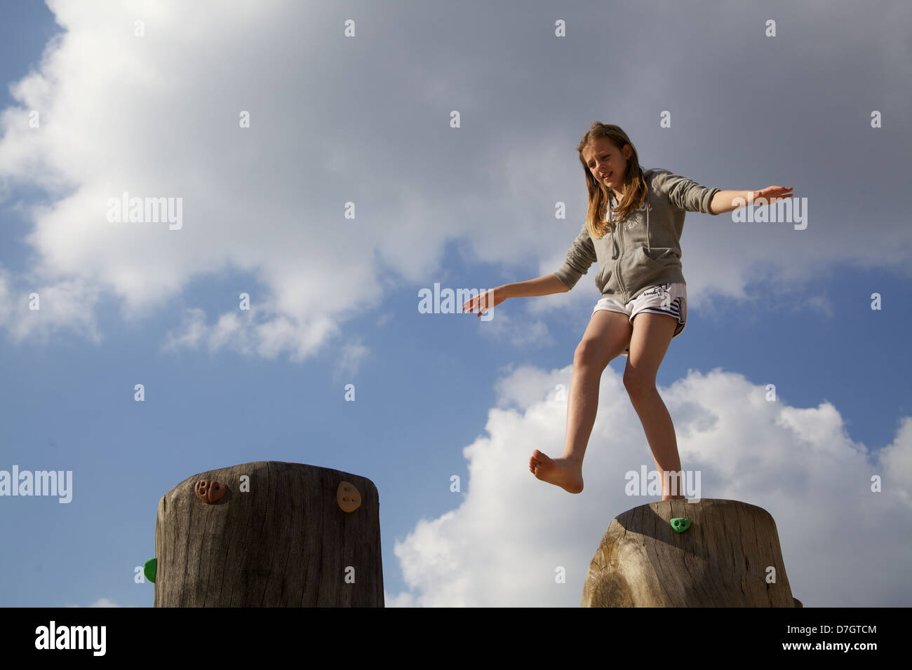 girl balancing on tree trunk attempting to take a wide step - Stock Image