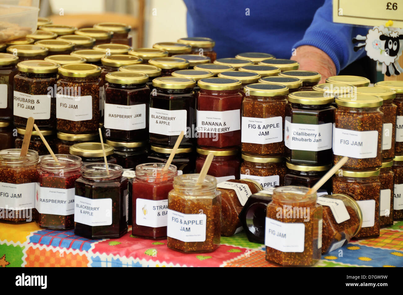 a display on a market stall showing many different kinds of jam on