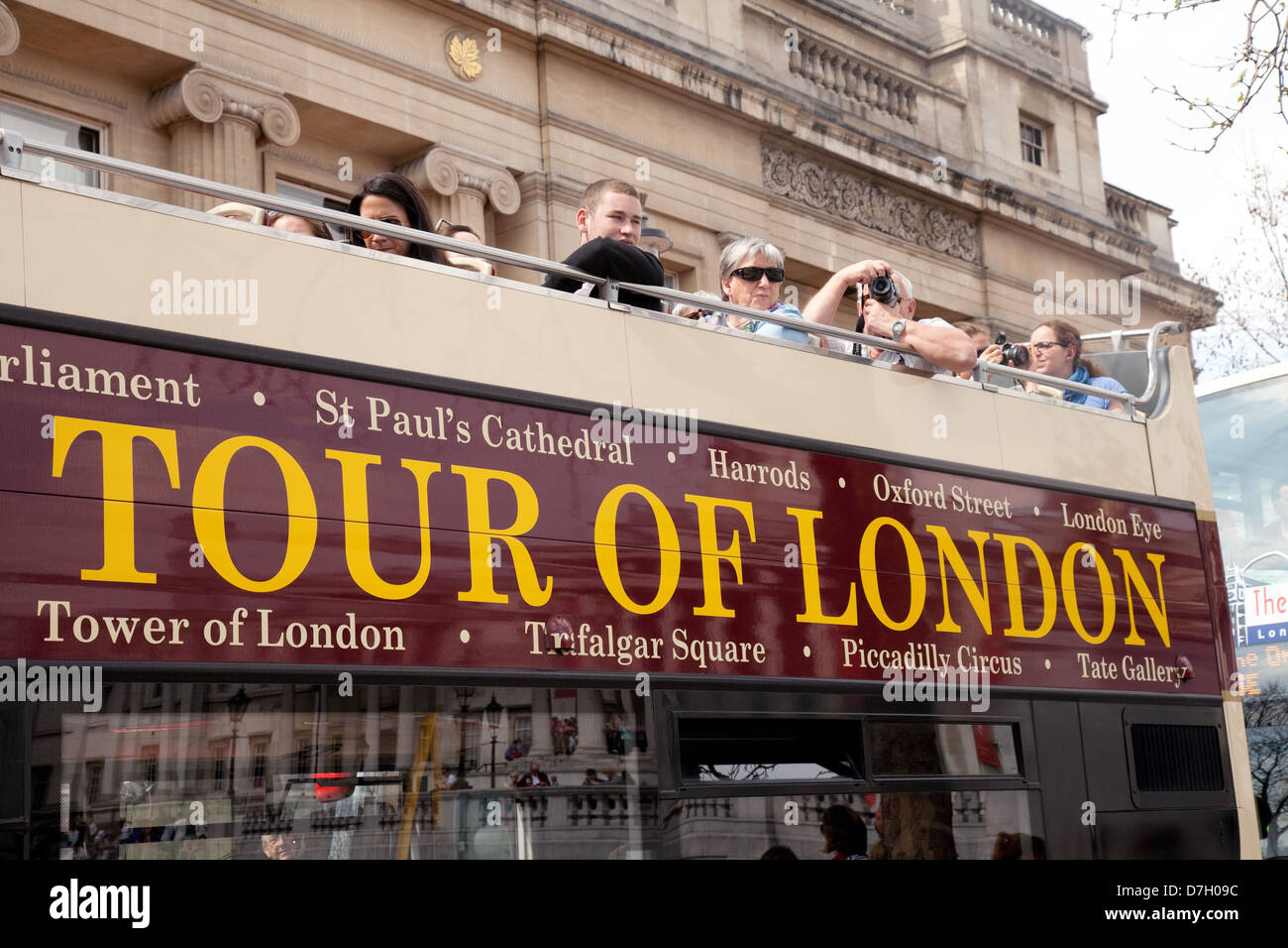 Tour of London sightseeing bus trip with tourists on the top deck, London England UK - Stock Image