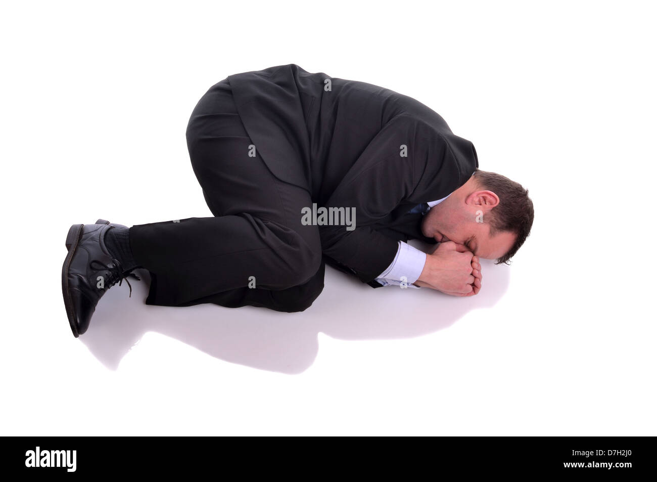 Businessman laying down in fetal position. Image is isolated on white - Stock Image