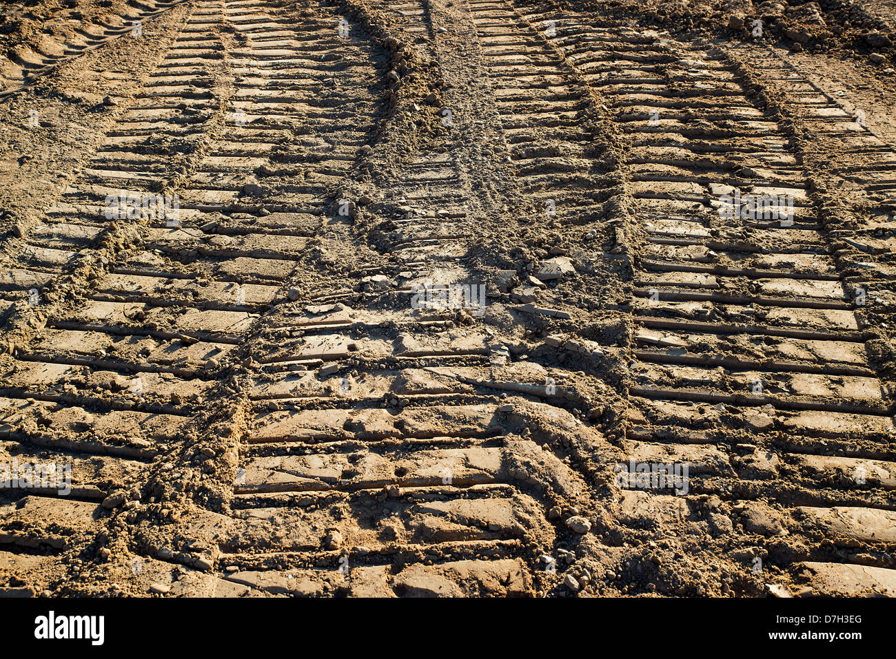 Tractor tracks in soil at housing construction site. - Stock Image