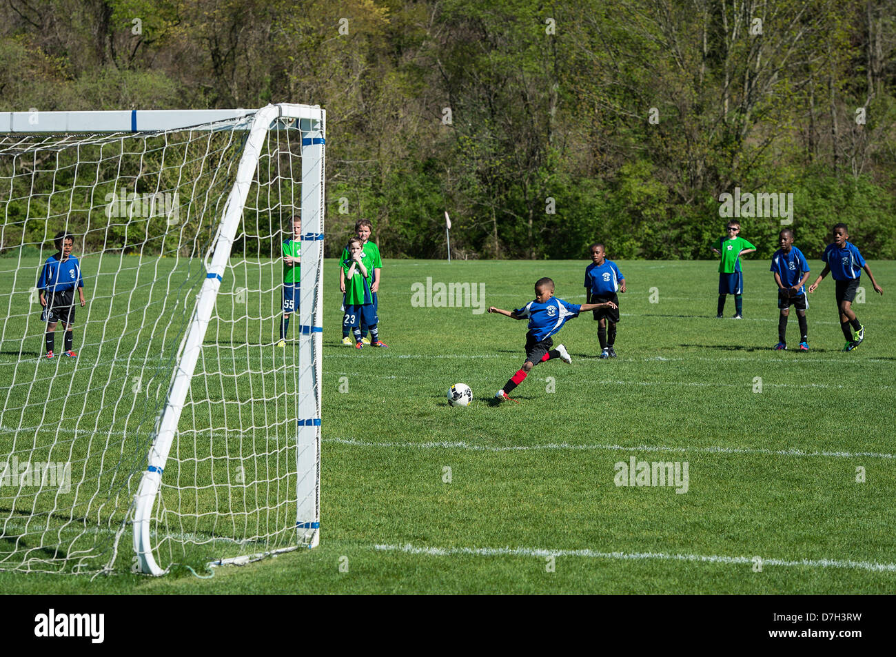 Young boy takes a penalty kick during soccer match. - Stock Image