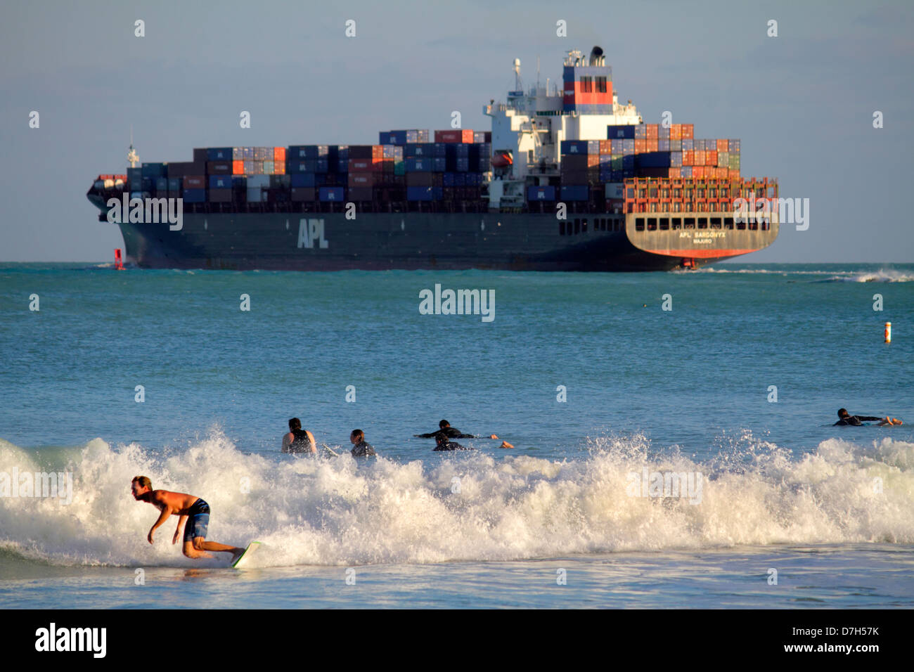 Miami Beach Florida Atlantic Ocean waves surf surfer surfboard riding man teen boy cargo container ship boat Stock Photo